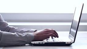Primer de manos y del teclado Vendedor que trabaja en el ordenador portátil metrajes