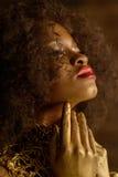Primer de maquillaje y de los accesorios del oro de la mujer americana africana o negra de la moda que lleva que presentan tocand Fotos de archivo libres de regalías