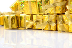 Primer de oro de los regalos en un blanco Imagenes de archivo
