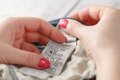 Primer de Person Reading The Clothing Label que muestra instrucciones de lavado foto de archivo libre de regalías