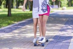 Primer de piernas de la muchacha caucásica y afroamericana Longboard patinador del adolescente al aire libre Fotos de archivo