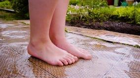 Primer de piernas femeninas La muchacha se coloca en el linóleo en un charco Momento fresco almacen de video