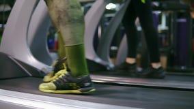 Primer de pies de corredores irreconocibles en el movimiento que caminan en las ruedas de ardilla en el gimnasio que calientan an almacen de video