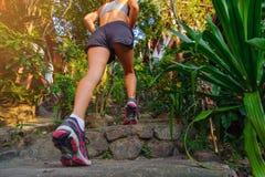 Primer de pies femeninos en las zapatillas de deporte que caminan al aire libre fotografía de archivo libre de regalías
