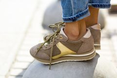 Primer de pies femeninos en zapatillas de deporte beige Mujer en de moda Foto de archivo