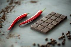 Primer de pimientas calientes, rojas al lado de una barra del chocolate oscuro MI imagen de archivo libre de regalías