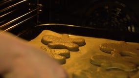 Primer de poner la cubierta con las galletas del hombre de pan de jengibre en horno metrajes