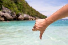 Primer de pulgares abajo y del gesto de la aversión en fondo de la orilla de mar de la playa Foto de archivo libre de regalías