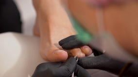 Primer de quitar cutículas de la uña del pie usando pinza del clavo Podadoras de la uña del pie Pedicura manual almacen de video