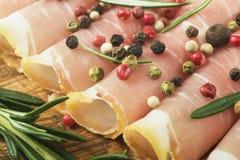 Primer de rebanadas finas de prosciutto con romero y paprika en tabla de cortar de madera Imagen de archivo libre de regalías
