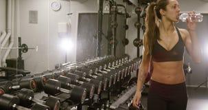 Primer de sudar a la mujer con el cuerpo del ajuste que camina en gimnasio de la aptitud almacen de video