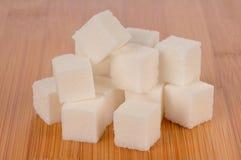 Primer de Sugar Cubes Piled en la madera de bambú Fotografía de archivo