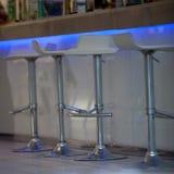 Primer de taburetes de bar en la barra iluminada Imagenes de archivo