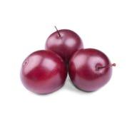 Primer de tres ciruelos rojos, aislado en un fondo blanco Ciruelo dulce y fresco Algunos ciruelos maduros Fruta de la pasión El v Imagenes de archivo