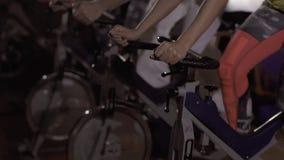 Primer de tres personas deportivas en el gimnasio que se resuelven en las bicicletas almacen de metraje de vídeo