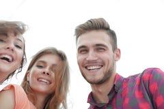 Primer de tres personas jovenes que sonríen en el fondo blanco Fotografía de archivo libre de regalías
