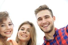 Primer de tres personas jovenes que sonríen en el fondo blanco Imagenes de archivo