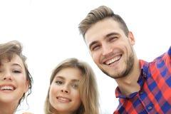 Primer de tres personas jovenes que sonríen en el fondo blanco Imágenes de archivo libres de regalías