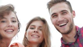 Primer de tres personas jovenes que sonríen en el fondo blanco Imagen de archivo