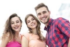 Primer de tres personas jovenes que sonríen en el fondo blanco Fotografía de archivo