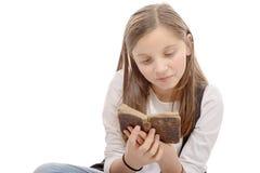 Primer de un adolescente joven que lee un libro, cruz-legge que se sienta Fotografía de archivo
