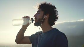 Primer de un agua potable apta del hombre joven después del ejercicio almacen de video