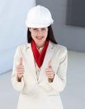 Primer de un arquitecto de sexo femenino con los pulgares para arriba fotografía de archivo libre de regalías