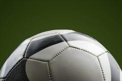 Primer de un balón de fútbol en un fondo verde fotos de archivo libres de regalías