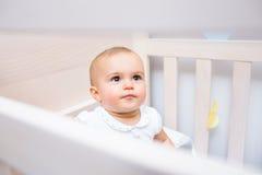 Primer de un bebé lindo que mira para arriba en pesebre Foto de archivo