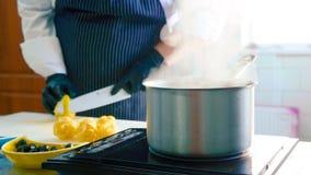 Primer de un cazo de cocido al vapor al vapor en una estufa cuando el cocinero limpia un limón Foto de archivo
