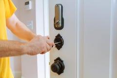 Primer de un cerrajero profesional que instala o que repara una nueva cerradura del deadbolt Fotografía de archivo