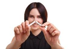Primer de un cigarrillo quebrado Mujer que rompe un cigarrillo aislado en un fondo blanco Concepto del tratamiento que fuma Fotografía de archivo libre de regalías