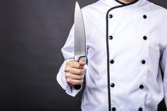 Primer de un cocinero que sostiene un cuchillo afilado grande imagen de archivo