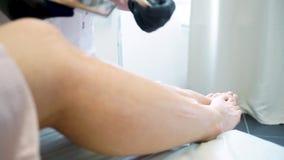 Primer de un cosmetólogo que encera la pierna de la mujer en balneario de la belleza Piernas femeninas y manos de la depilación d metrajes