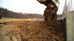 Primer de un cubo del excavador que lanza hacia fuera la tierra Cámara lenta de un cavador que cava un hoyo y que lanza la sucied almacen de video