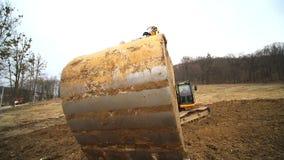 Primer de un cubo del excavador que lanza hacia fuera la tierra C?mara lenta de un cavador que cava un hoyo y que lanza la sucied almacen de metraje de vídeo