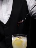 Primer de un desmoche de colada del camarero en un cóctel en un fondo negro Party las bebidas Concepto de la preparación del cóct imágenes de archivo libres de regalías