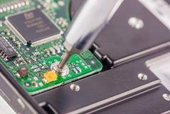Primer de un destornillador y de una placa de circuito Foto de archivo