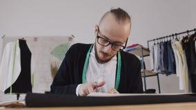 Primer de un diseñador o de un sastre beared jóvenes en las lentes que se sientan en un workplase en el estudio y que tallan metrajes