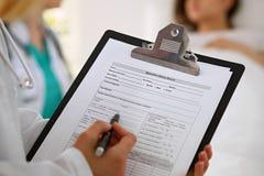 Primer de un doctor de sexo femenino mientras que llena encima de expediente del historial médico imagen de archivo libre de regalías