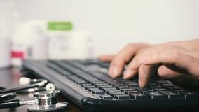 Primer de un doctor de sexo masculino que usa un teclado de ordenador almacen de video