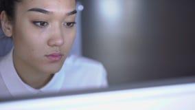 Primer de un empleado de sexo femenino asiático que mira el monitor y el trabajo almacen de metraje de vídeo