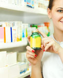 Primer de un farmacéutico de sexo femenino borroso que sostiene hacia fuera las tabletas en BO Imagen de archivo libre de regalías