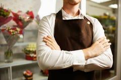 Primer de un florista confiado en un delantal marrón en un fondo de la tienda Concepto uniforme del florista imagen de archivo