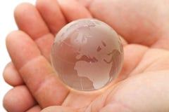 Globo de cristal en manos Fotografía de archivo