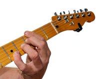 Primer de un guitarrista Fingering Chords contra un fondo blanco fotos de archivo libres de regalías