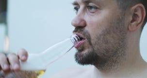 Primer de un hombre con una cerveza de consumición de la barba de una botella de cristal almacen de video