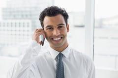 Primer de un hombre de negocios elegante sonriente usando el teléfono móvil Fotos de archivo libres de regalías