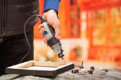 Primer de un hombre del hardworker que perfora un marco de madera con su taladro, con los accesorios de la perforación sobre una  Fotografía de archivo