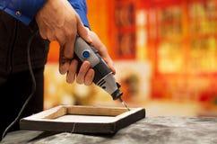 Primer de un hombre del hardworker que perfora un marco de madera con su taladro, con los accesorios de la perforación sobre una  Imagenes de archivo